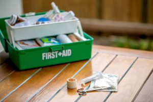 First aid kit on the table in the garden, green box